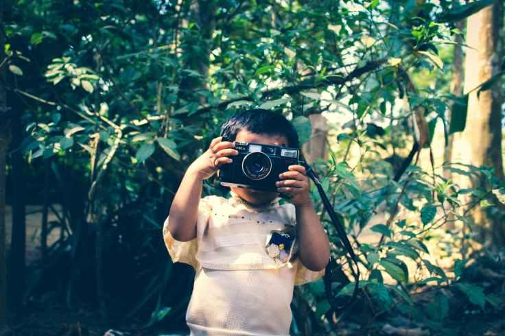 boy holding black flash camera near green leaf plants